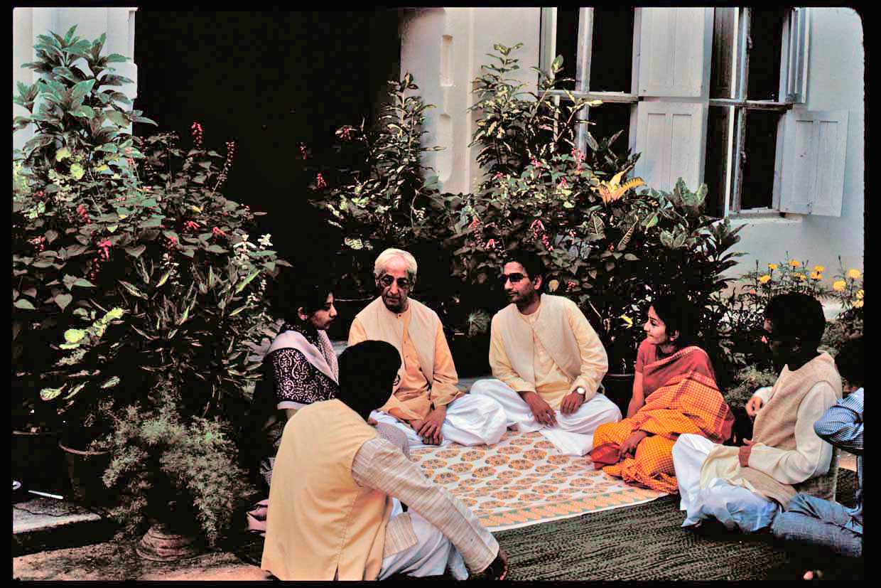 Krishnaji speaking with staff at Rishi Valley, in front of the old guest house. Narayan is sitting to the left of Krishnaji. Copyright Mary Zimbalist.
